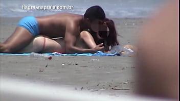 Namorados fodem disfarçadamente na areia da praia