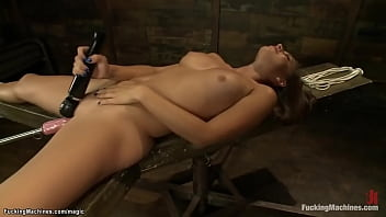 Tied and blindfolded sexy brunette babe Rilynn Rae with legs bent in knees and wide opened gets shaved pussy fucked by machine in bed