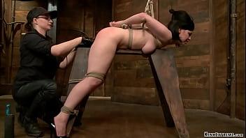Brunette lesbian slave Belle Noire gets crotch rope bondage then bent over with hands tied behind back and bar behind her elbows gets finger fucked