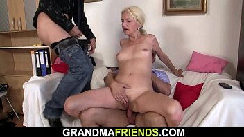 Old blonde woman swallows two cocks at once