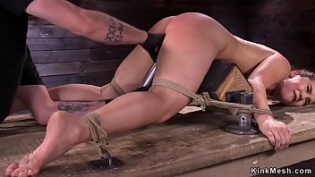 Gagged brunette slave in rope bondage gets pussy fucked with dick on a stick