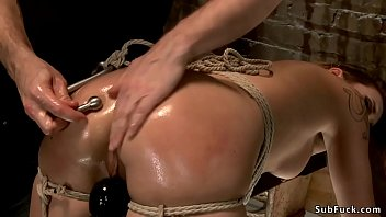 Hot gagged brunette slave Andre Shakti in tight rope bondage and slightly bent forward gets whipped then ass oiled and hooked with steel on hogtie