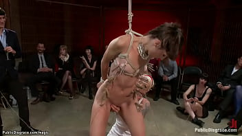 Tied and zippered brunette slut Kristine Kahill gets pussy fingered by blond lezdom Lorelei Lee then sprinkled with milk and group fucked in public
