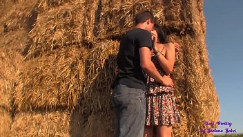 Her short skirt and her giant tits turn the guy on as he fucks her on the hay bales