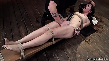 Brunette curly slave Victoria Voxxx is hung for one leg while hands are tied to other in upside down suspension gets tormented and punched on hogtie