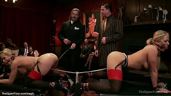 Two hot MILF slaves Holly Heart and Simone Sonay are put through a grueling predicaments and rough sex and humiliation in the Upper Floor bdsm party