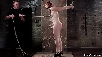 Watch Redhead sub Amarna Miller in standing bondage with arms tied up behind back gets nipples clamped and pulled by rope then in backbend position whipped preview