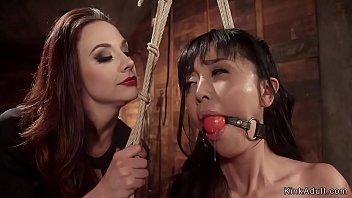 Brunette mistress Chanel Preston in red fishnet finger fucks petite Asian slave Marica Hase in rope bondage then fingers her ass