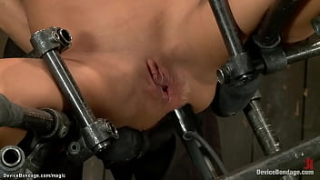 Sexy gagged brunette slave Ariel X in pink lingerie is straddled on wooden pony with hands in strappado gets whipped then in metal device anal machine fucked