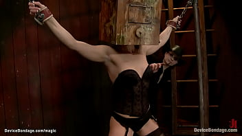 Bound blonde lesbian slave Ash Hollywood in black stockings with trapped head in wooden box gets nipples tormented and pussy vibed by lezdom Claire Adams