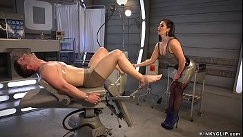 Brunette femdom Lea Lexis in tight grey latex dress whips strapped little man slave Rick Fantana then toys and fingers his ass in various positions