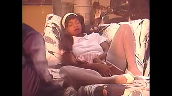 Young black girl in a white headband fucks on the couch with a big black guy