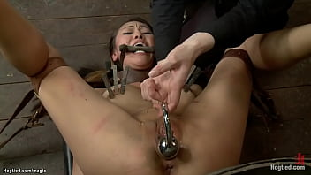 Bound Asian lesbian slave Jayden Lee in sitting position with exposed butt gets anal plugged then caned in pile driver and whipped in old bed without mattress by  lezdom Claire Adams