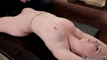Gagged pale blobnde slave Darcie Belle in rope bondage with hands behind back gets shaved pussy vibrated then takes crotch rope and whip