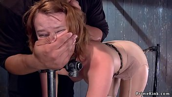 Hot ass redhead slut Claire Robbins is locked in metal device bondage bent forward in standing doggy style position and gets vibrated then chained