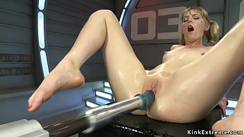 Blonde babe Mona Wales takes of shoes and lifts up skirt then gets red dildo machine in standing bent forward position from behind while rubs clit