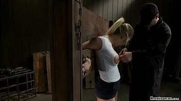Hot big tits blonde Holly Heart is locked in stock wall and tongue and nipples clamped then in doggy style device bondage hard whipped by master Orlando