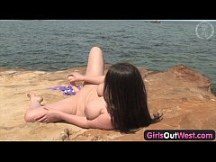 Attractive brunette babe Angie rubs her shaved pussy and masturbates with a realistic dildo on beach