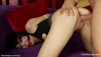 Gagged brunette babe with hands tied behind back Coral Aorta is humiliated by dom Princess Donna Dolore and rough fucked by big cock Mr Pete in public tattoo shop
