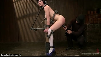 Bound in slightly squat position and butt plugged slave Proxy Paige gets nipples tormented then strapped and candle waxed and ass toyed by master Orlando on device bondage